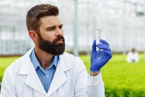 Nachdenklicher Mann Forscher hält eine Glasröhre