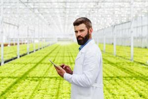 männlicher Forscher, der Pflanzen mit einer Tablette studiert
