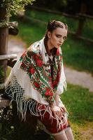 junges Mädchen in einem traditionellen ukrainischen Kleid sitzt auf einer Bank im Park