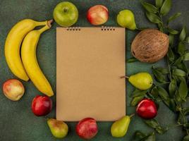 sortierte Frucht um Notizblock auf grünem Hintergrund