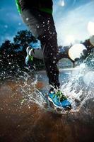 eine Person, die mit blauen Schuhen im Regen läuft foto