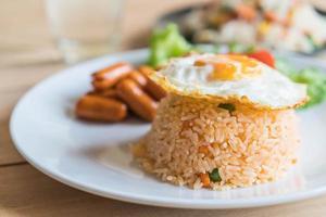 Teller mit Spiegelei, Reis und Wurst darauf