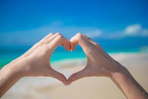 Person, die ein Herz mit den Händen am Strand macht