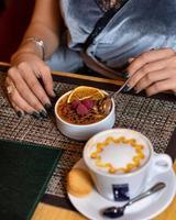 Frau, die Himbeerdessert mit Lattekaffee isst