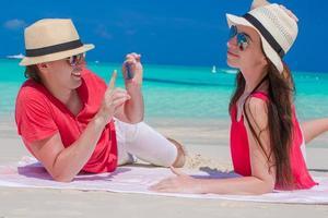 Mann, der ein Foto einer Frau an einem Strand macht