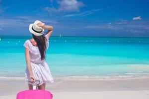 Frau, die einen Koffer am Strand zieht foto