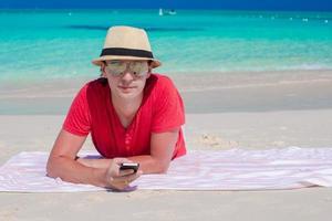 Mann, der mit seinem Telefon am Strand liegt
