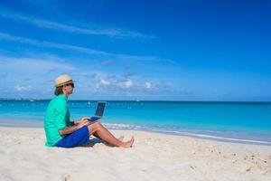 Mann, der an einem Laptop am Strand arbeitet