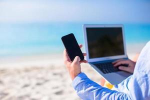 Nahaufnahme einer Person, die ein Telefon und einen Laptop am Strand benutzt