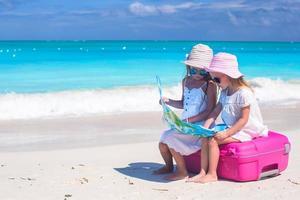 zwei Mädchen sitzen auf einem Koffer am Strand und betrachten eine Karte