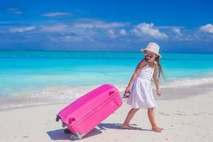Mädchen, das einen rosa Koffer an einem Strand zieht foto