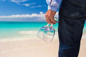 Nahaufnahme einer Person, die Brille am Strand hält