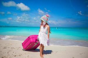Mädchen in Wintermütze und Fäustlinge, die mit Gepäck auf einem Strand gehen