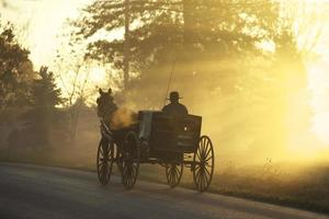 Silhouette eines Mannes, der auf einer Kutsche auf Betonstraße reitet