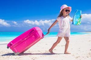 Mädchen, das einen Koffer zieht und eine Karte an einem Strand hält foto