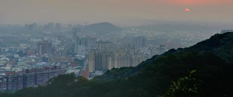 Blick auf eine Stadt bei Sonnenuntergang von einem Berg foto