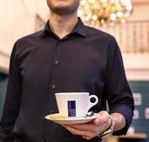 Kellner hält eine Tasse Kaffee im Restaurant
