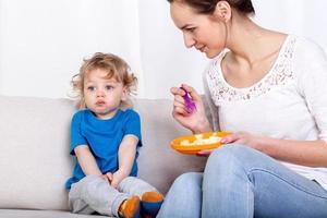 Mutter füttert Kind auf der Couch foto