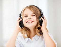 lächelndes kleines Mädchen mit Kopfhörern, die Musik hören foto