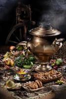 Stillleben mit Samowar, Obst, Tee und Spinnrad foto