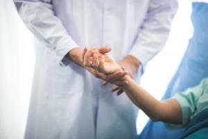 Nahaufnahme des Arztes, der die Hand eines Patienten hält foto