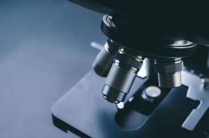Nahaufnahme eines wissenschaftlichen Mikroskops mit Metalllinse, Datenanalyse im Labor