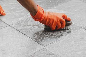 Person mit orangefarbenen Reinigungshandschuhen, die den Boden schrubben