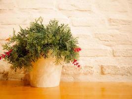 Blume im Topf auf Holztisch weißem Backsteinmauerhintergrund foto