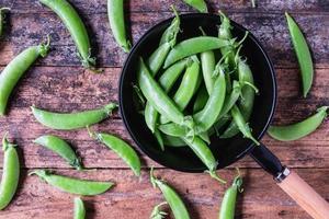 frische grüne Erbsen in der Pfanne auf dem Küchentisch