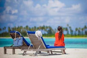 Frau sitzt auf einem Liegestuhl am Strand