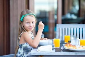 Mädchen lächelt am Frühstückstisch