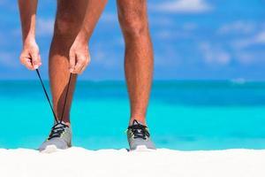 männlicher Lauf, der seine Schuhe bindet