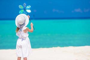 Mädchen mit einem Windrad am Strand foto