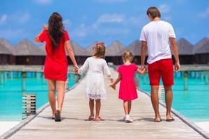 Malediven, Südasien, 2020 - Familie geht auf einem Dock in einem Resort spazieren foto