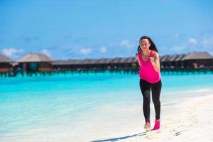 Malediven, Südasien, 2020 - Frau läuft an einem Strand in der Nähe eines Resorts foto