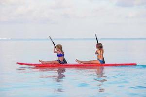 zwei Mädchen paddeln