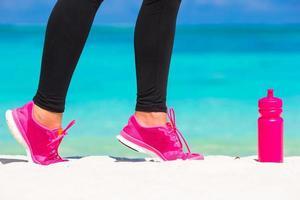 Frau in rosa Schuhen am Strand