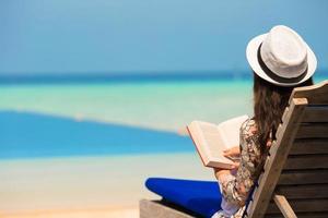 Frau liest ein Buch in der Nähe eines Pools foto
