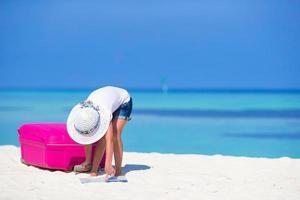 Mädchen, das eine Karte auf einem Strand betrachtet