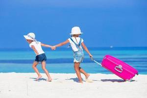 zwei Mädchen, die mit Gepäck an einem Strand laufen foto