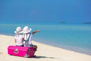 zwei Mädchen sitzen auf Gepäck am Strand foto