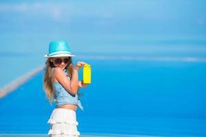 Mädchen, das Sonnencreme an einem Strand hält foto