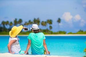 glückliches Paar, das ein Selfie am Strand nimmt