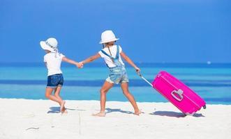 zwei Mädchen, die mit Gepäck am Strand spazieren gehen foto