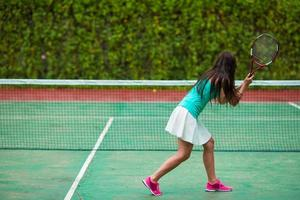 Frau, die Tennis auf einem Tennisplatz spielt foto