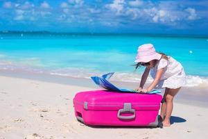 Mädchen mit rosa Koffer und einer Karte auf einem tropischen Strand