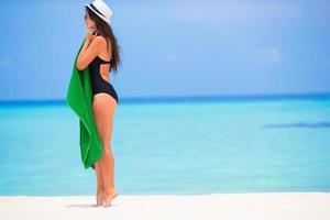 Frau hält ein Handtuch an einem weißen Sandstrand