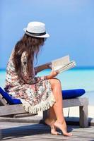 Frau, die ein Buch während eines Strandurlaubs liest foto