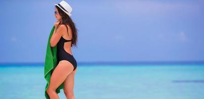 Frau hält ein Handtuch am Strand