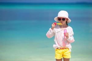 Mädchen bläst Blasen an einem Strand foto
